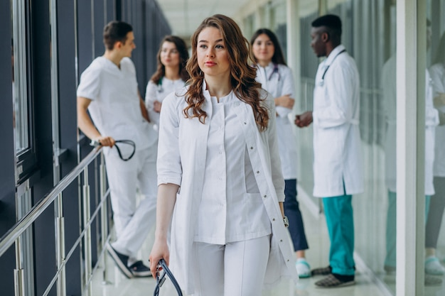 Joven doctora caminando por el pasillo del hospital