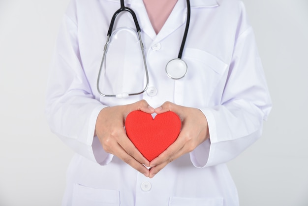 Joven doctora con estetoscopio con corazón rojo en sus manos sobre blanco