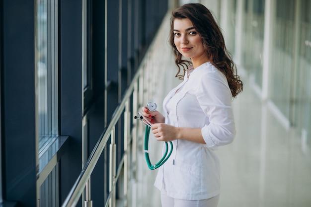 Joven doctora con estetoscopio en el hospital