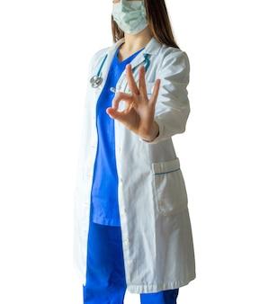 Joven doctora exitosa en un uniforme médico azul y una máscara que muestra el signo correcto