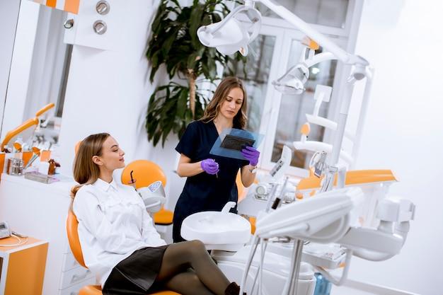 Joven doctora con guantes protectores examinar radiografía con su paciente en el consultorio del dentista