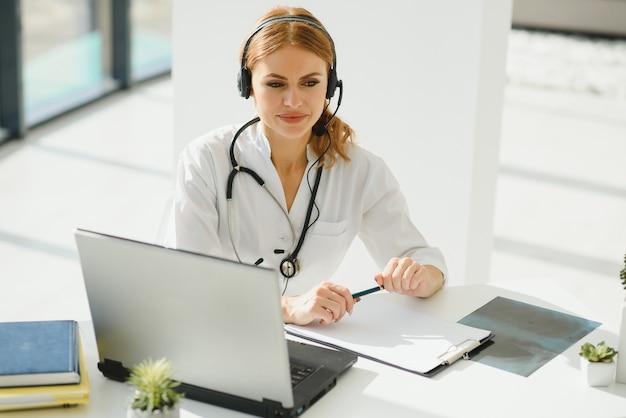 Joven doctora hablando con el paciente en línea desde el consultorio médico. cliente consultor médico en portátil de chat de video en el hospital