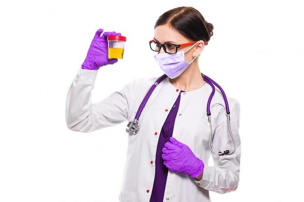 Joven doctora hermosa con muestra de orina en sus manos en máscara médica y guantes estériles