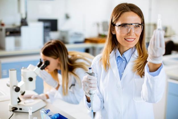 Joven doctora con mascarilla protectora en el laboratorio con matraz con muestra líquida