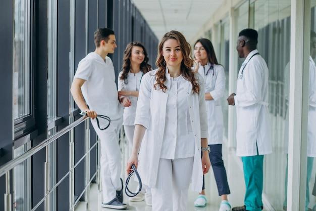 Joven doctora posando en el pasillo del hospital