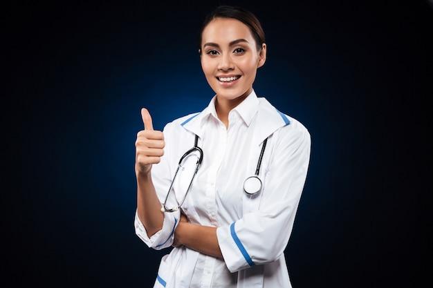 Joven doctora positiva con estetoscopio mostrando el pulgar hacia arriba