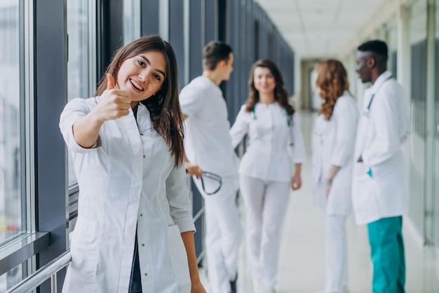 Joven doctora con pulgares arriba gesto, de pie en el pasillo del hospital