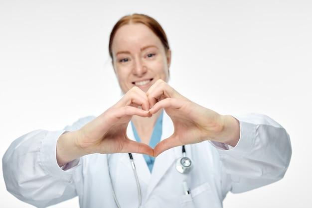 Joven doctora sonriente haciendo signo de corazón con las manos. foto de alta calidad