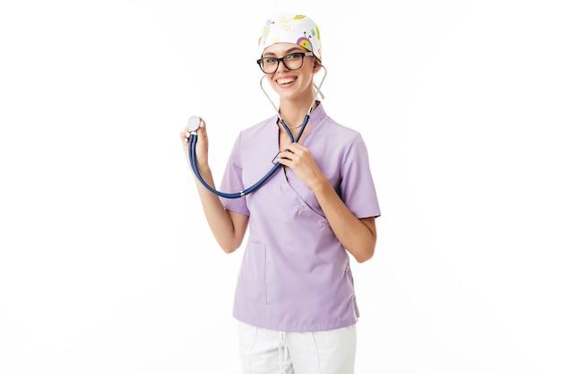 Joven doctora sonriente en uniforme y anteojos usando fonendoscopio mientras con alegría