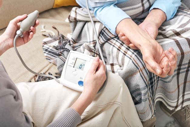 Joven doctora con tonómetro midiendo la presión arterial del anciano jubilado cubierto por plaid mientras está sentado en el sofá