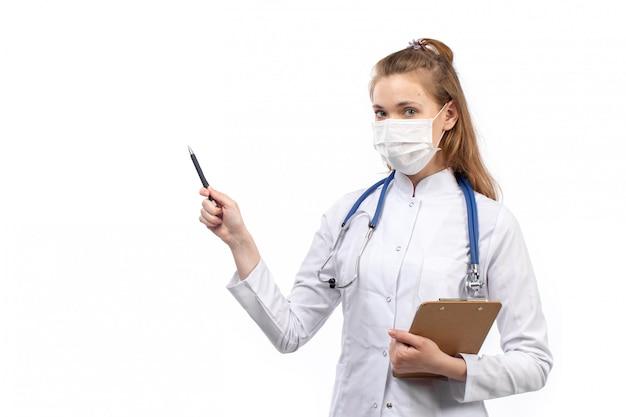 Joven doctora en traje médico blanco con estetoscopio en máscara protectora blanca escribiendo notas sobre el blanco