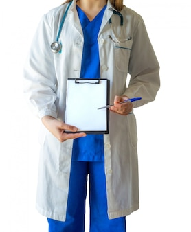 Joven doctora en un uniforme médico azul apuntando a un papel blanco en blanco