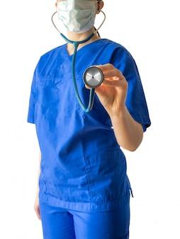 Joven doctora en un uniforme médico azul sosteniendo un estetoscopio aislado sobre un fondo blanco.