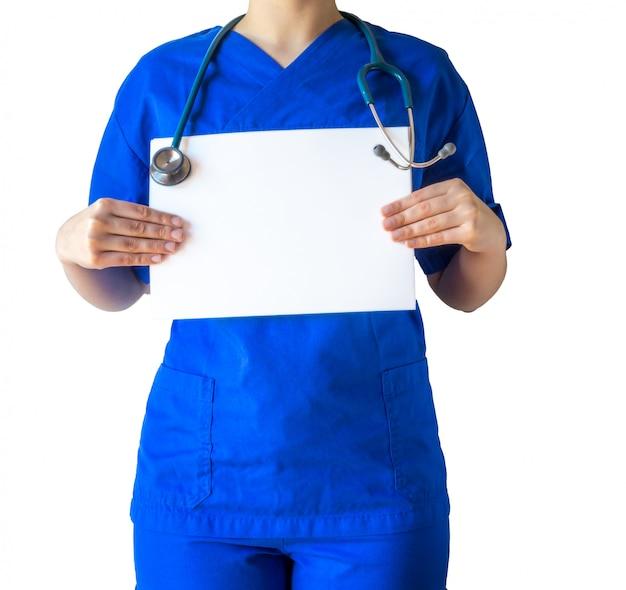 Joven doctora en un uniforme médico azul sosteniendo un libro blanco en blanco con un espacio de copia
