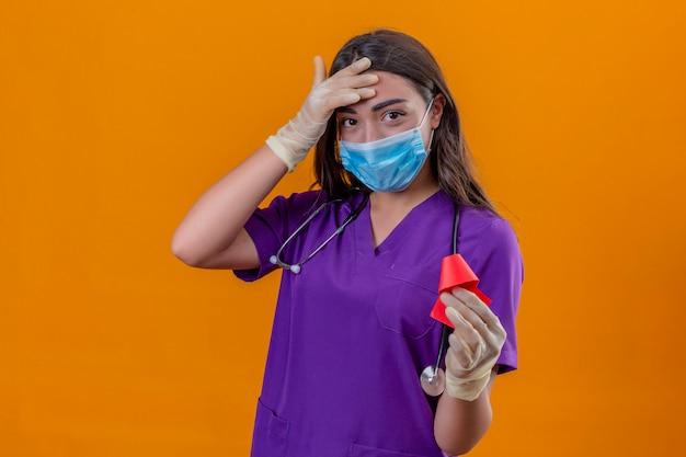 Joven doctora en uniforme médico con fonendoscopio con máscara protectora y guantes sonriendo sosteniendo la cinta roja y tocando la frente con la mano de pie sobre fondo naranja aislado