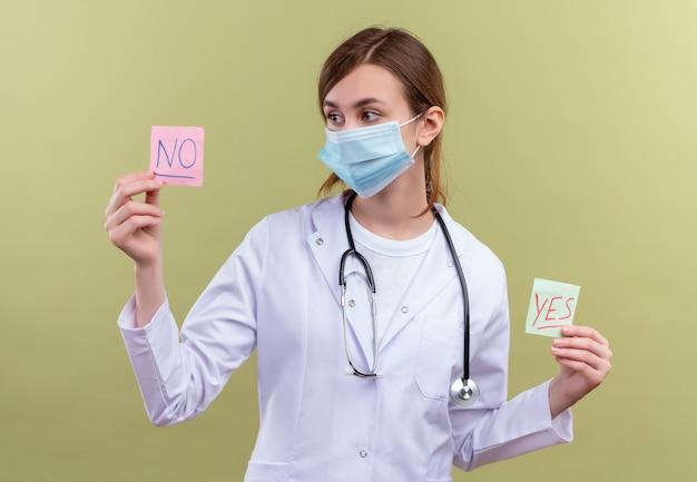 Joven doctora vistiendo bata médica, máscara y estetoscopio sosteniendo notas de sí y no y mirando ninguna nota en la pared verde aislada