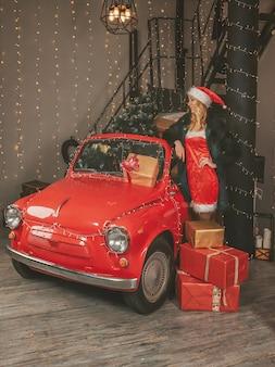Joven doncella de nieve bonita en decoraciones festivas y un auto rojo con regalos y árbol de navidad