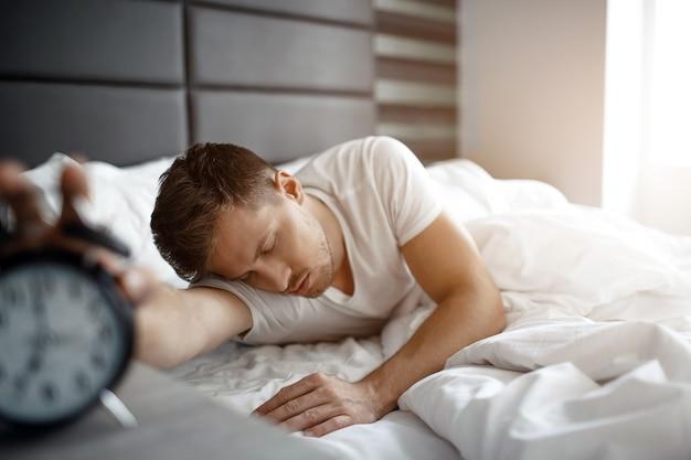 Joven dormir en la cama por la mañana. él sostiene la mano en el reloj. dormir demasiado. luz.