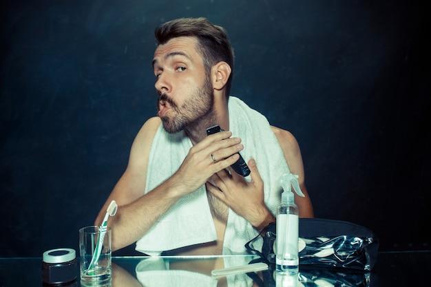 El joven en el dormitorio sentado frente al espejo rascándose la barba en su casa. concepto de emociones humanas