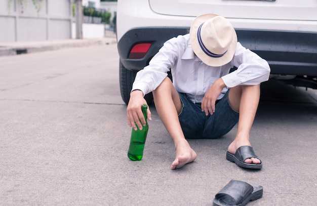 Joven durmiendo detrás de su coche después de beber cerveza demasiado en la fiesta de anoche