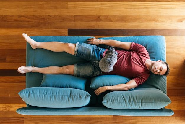 Joven durmiendo en el sofá en casa con conejito