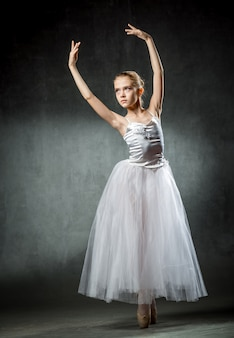 Joven e increíblemente hermosa bailarina posando y bailando en el estudio.