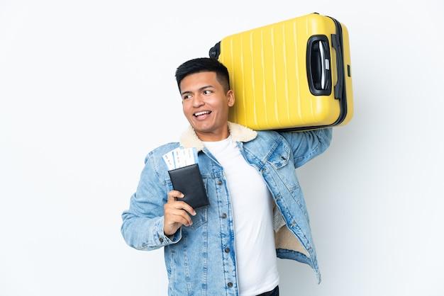 Joven ecuatoriano aislado sobre fondo blanco en vacaciones con maleta y pasaporte