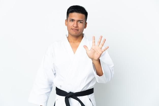 Joven ecuatoriano haciendo karate aislado sobre fondo blanco contando cinco con los dedos