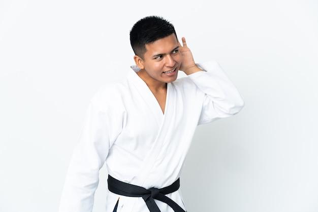 Joven ecuatoriano haciendo karate aislado sobre fondo blanco escuchando algo poniendo la mano en la oreja