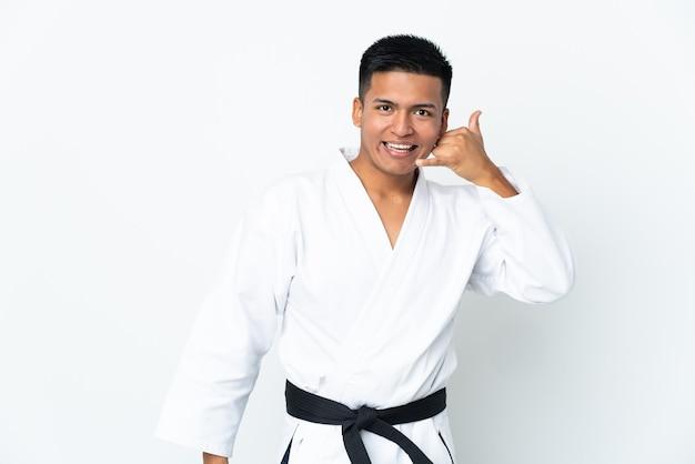 Joven ecuatoriano haciendo karate aislado sobre fondo blanco haciendo gesto de teléfono. llámame señal