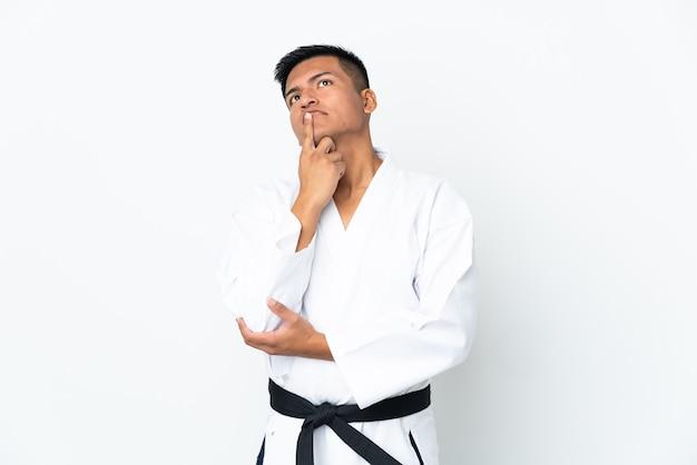 Joven ecuatoriano haciendo karate aislado sobre fondo blanco teniendo dudas mientras mira hacia arriba
