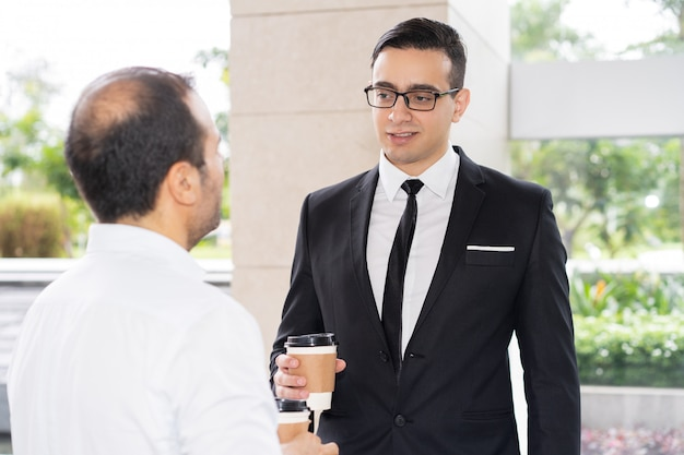 Joven ejecutivo confía en gafas hablando con su colega
