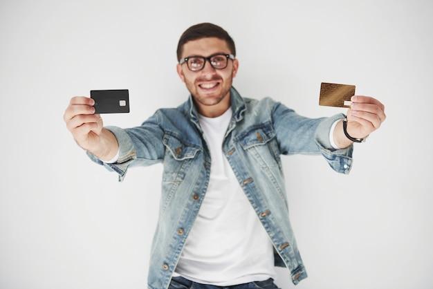 Joven ejecutivo de negocios masculino guapo en vestimenta casual con una tarjeta de crédito en los bolsillos en blanco