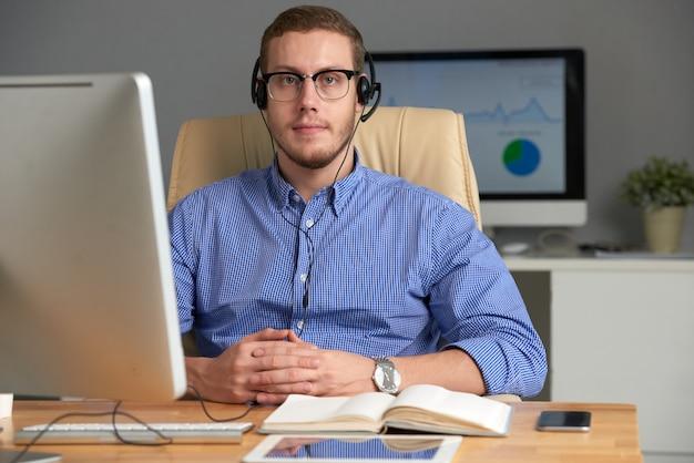 Joven ejecutivo de negocios usando auriculares mirando a la cámara