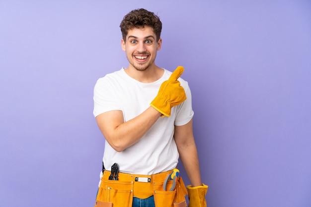 Joven electricista hombre sobre pared púrpura apuntando con el dedo al lado