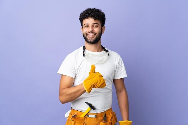 Joven electricista marroquí aislado en la pared púrpura dando un pulgar hacia arriba gesto