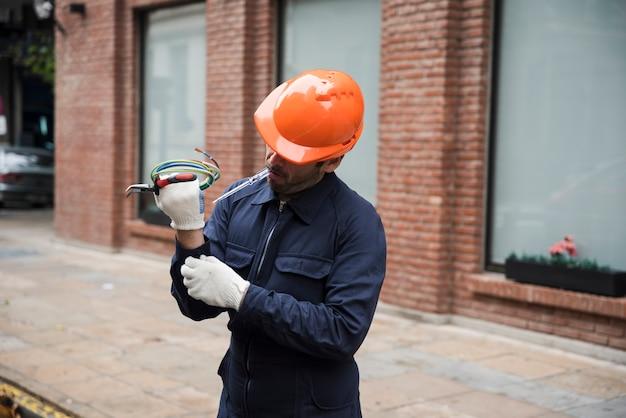 Joven electricista mirando mano manga en el trabajo