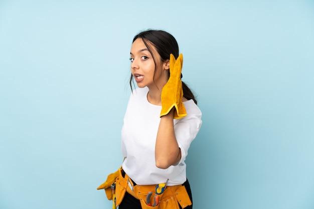 Joven electricista mujer en la pared azul escuchando algo poniendo la mano en la oreja
