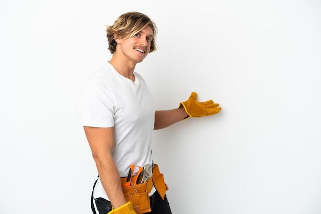 Joven electricista rubio aislado en blanco extendiendo las manos hacia un lado para invitar a venir