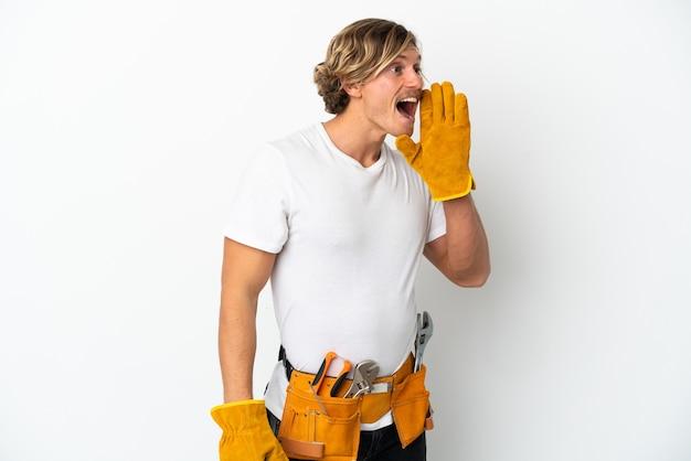 Joven electricista rubio aislado en blanco gritando con la boca abierta hacia un lado