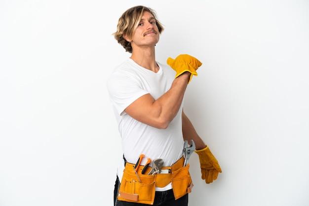 Joven electricista rubio aislado en la pared blanca orgulloso y satisfecho de sí mismo