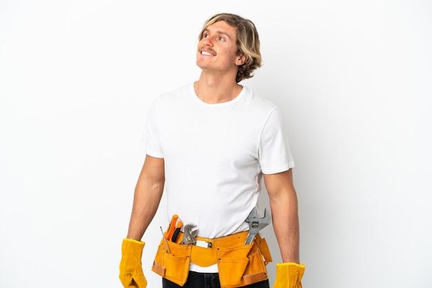 Joven electricista rubio aislado sobre fondo blanco pensando en una idea mientras mira hacia arriba
