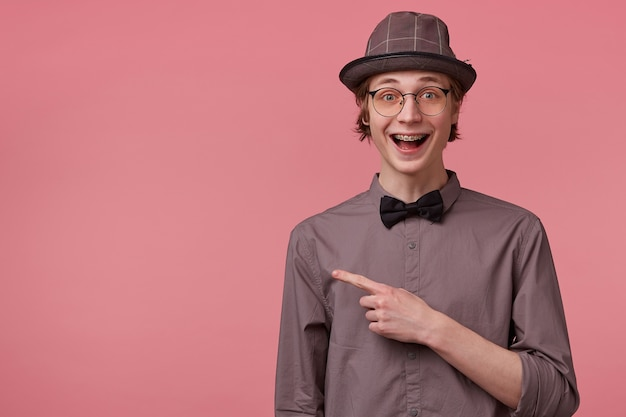Un joven elegante abrió la boca con entusiasmo, está abrumado por emociones positivas, felicidad, alegría aislada en rosa, apuntando con el dedo índice a la izquierda en el espacio de la copia