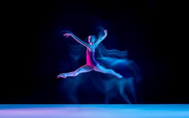 Joven y elegante bailarina de ballet aislada sobre fondo de estudio púrpura en luz de neón