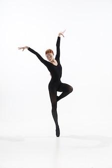 Joven y elegante bailarina de ballet en estilo minimalista negro aislado en blanco