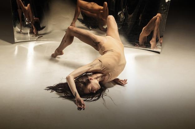 Joven y elegante bailarina de ballet moderno en pared marrón con espejo
