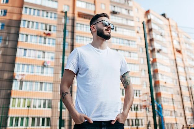 Joven elegante con barba en una camiseta blanca y gafas