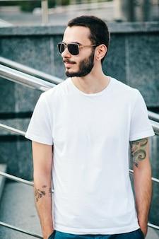 Un joven elegante con barba en una camiseta blanca y gafas