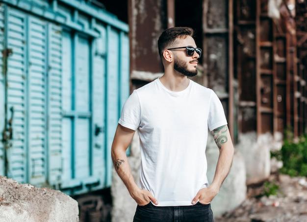 Un joven elegante con barba en una camiseta blanca y glasse