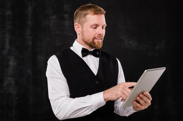 Joven elegante camarero de elegante restaurante desplazándose en tableta mientras busca menú sobre fondo negro